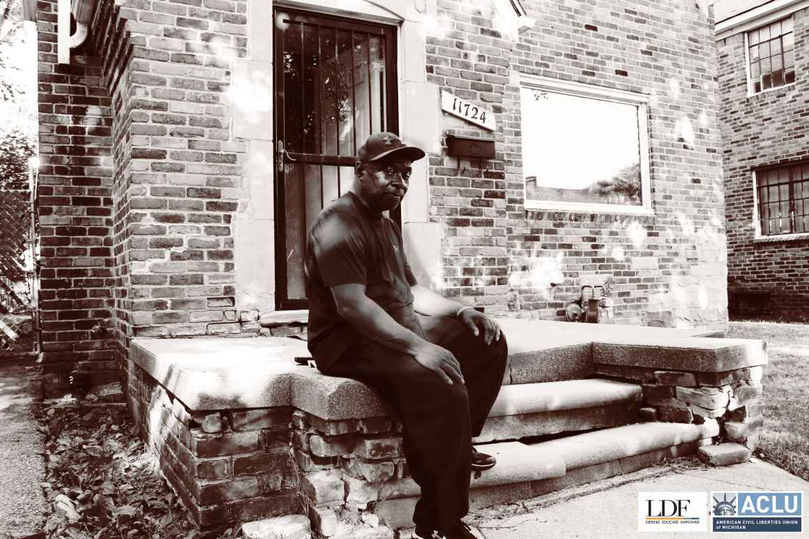 Walter Hicks sits on his home's stopp. He looks at the camera with his hands on his knees, one foot propped on a step.