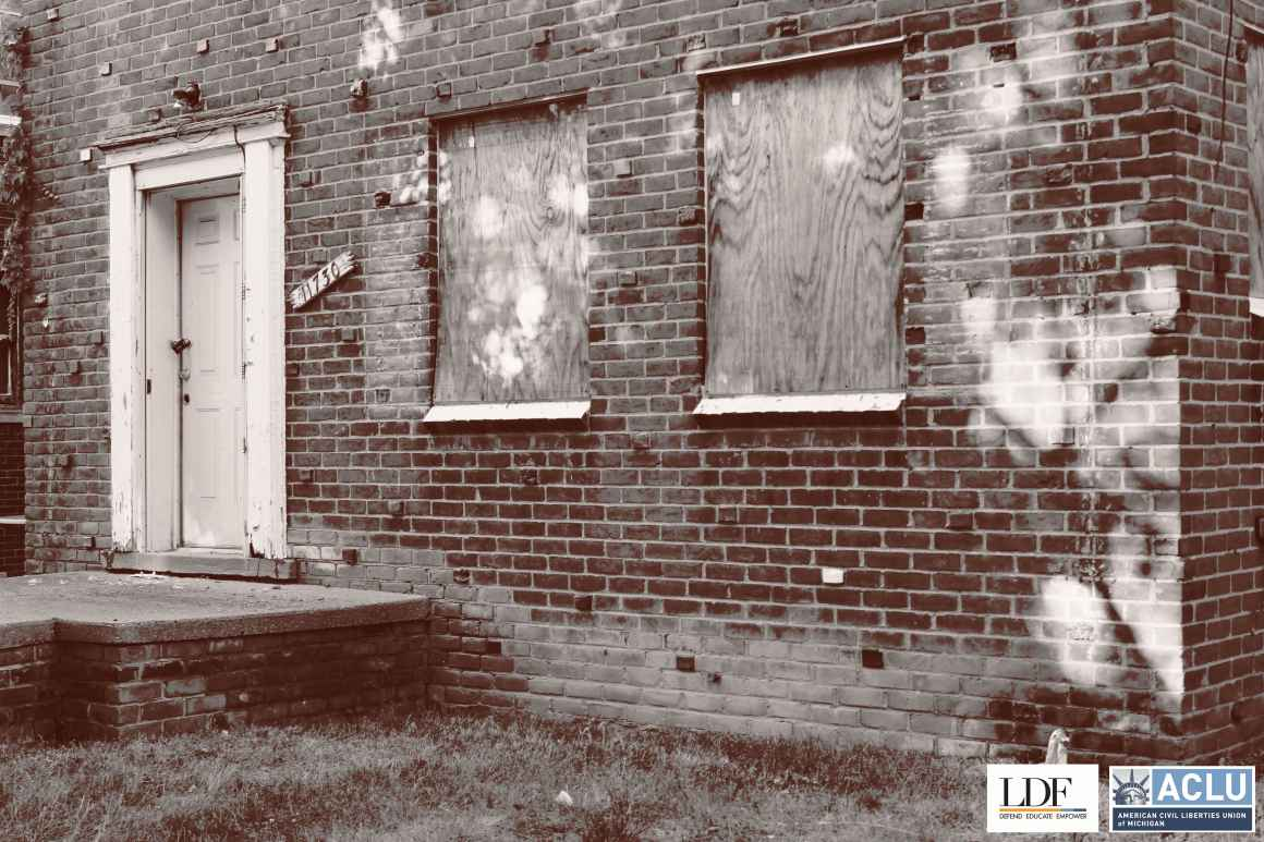 A foreclosed house with boarded up windows.