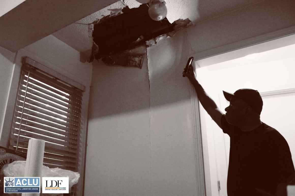 Walter Hicks holds a cellphone flashlight up to a drop ceiling with a hole in it and a crack running down the wall