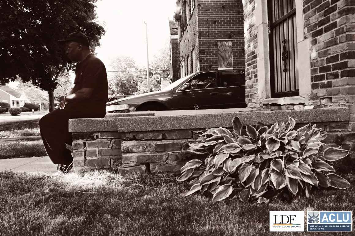 Walter Hicks sits on his stoop in front of his house looking towards the street.