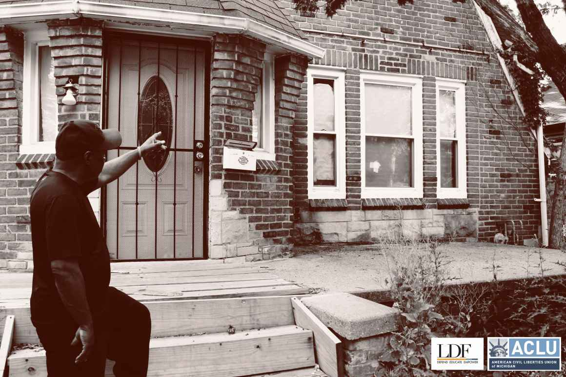 Walter Hicks points towards his foreclosed house.