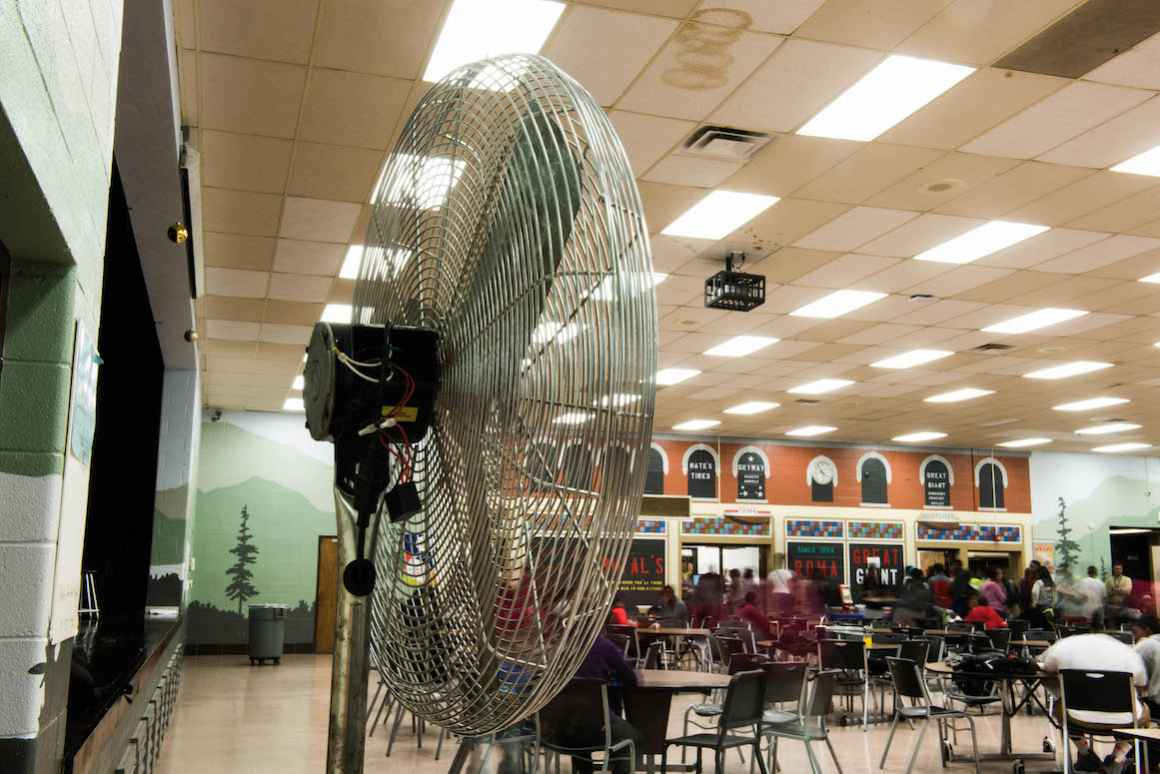 At Beecher High School, the lack of air conditioning requires staff to use large fans. With only a few fans, purchased from the school's general fund, staff must move these fans around, depending on where students are in any given moment.