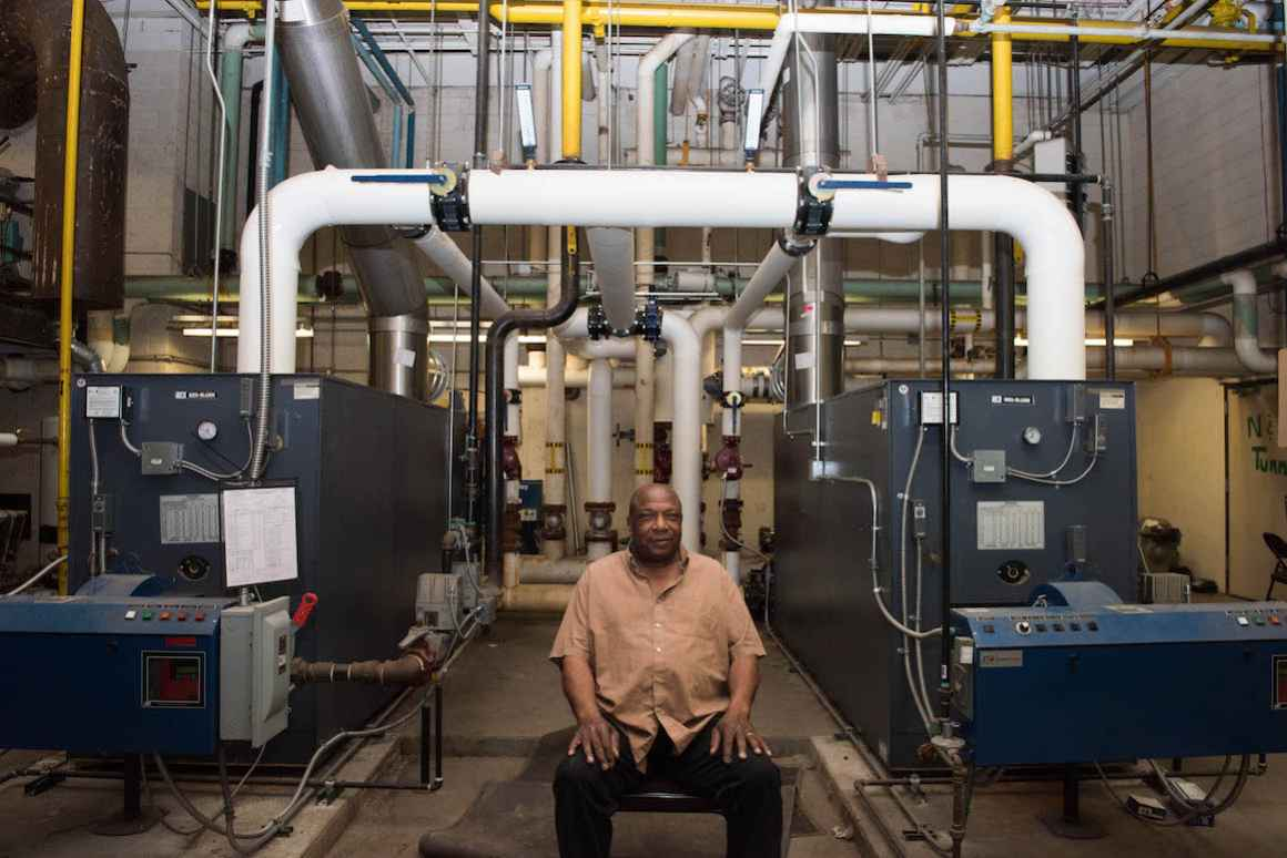 Sam Bell, a custodian at Beecher High School and General Motors retiree, sits in front of the school's antiquated steam heating system.