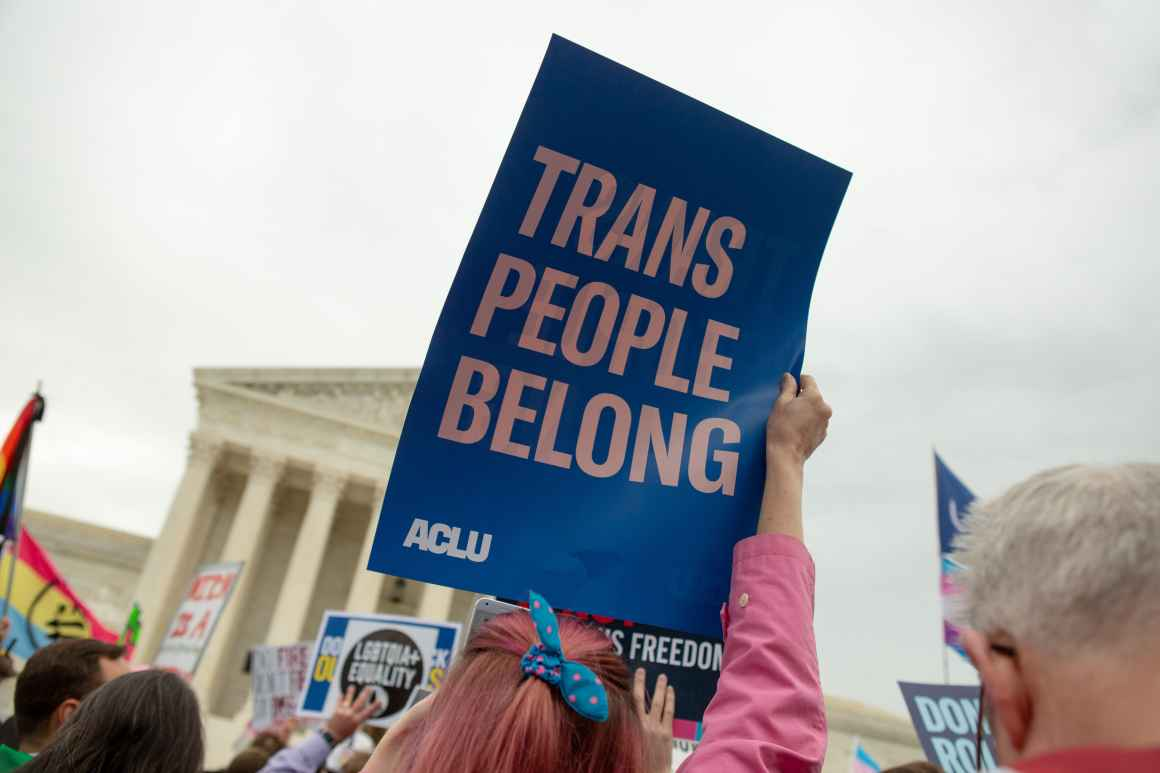 An activist holds up a sign that reads 'Trans People Belong'
