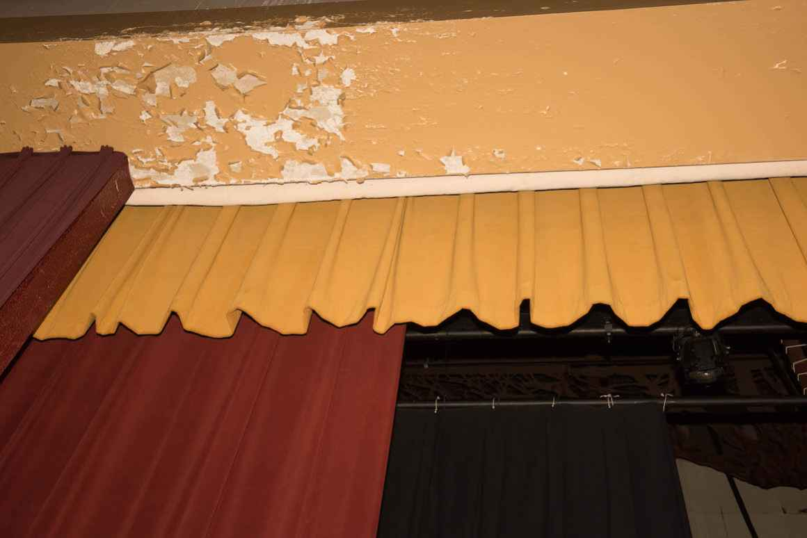 Plaster flakes off of the walls inside the 1960s-era auditorium at Muskegon High School.
