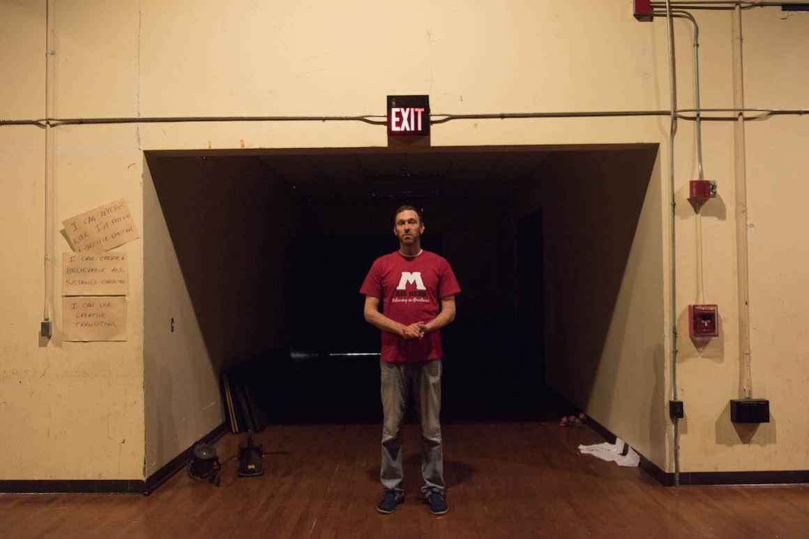Kirk Carlson, graduate of Muskegon High School and the school's current theater teacher and stage manager, stands in front of the school aging auditorium