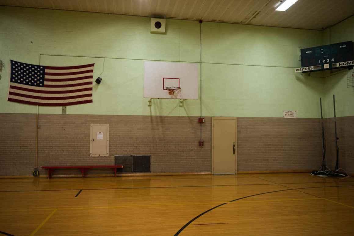 The gym at Nelson Elementary school features old basketball hoops that are not safeguarded from detaching from the wall if a child hangs from the rim