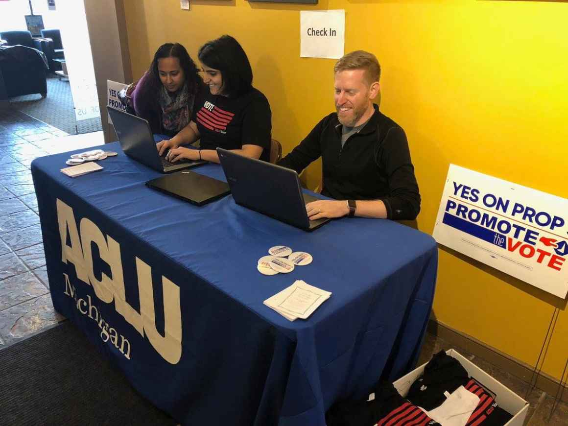 Three volunteers at sign-in table at ACLU of Michigan