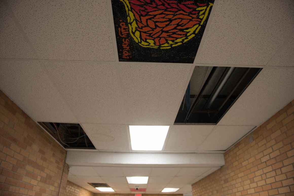 As an art activity, students paint the particle board on the ceiling to conceal the brown water stains left by the school's leaking roof.