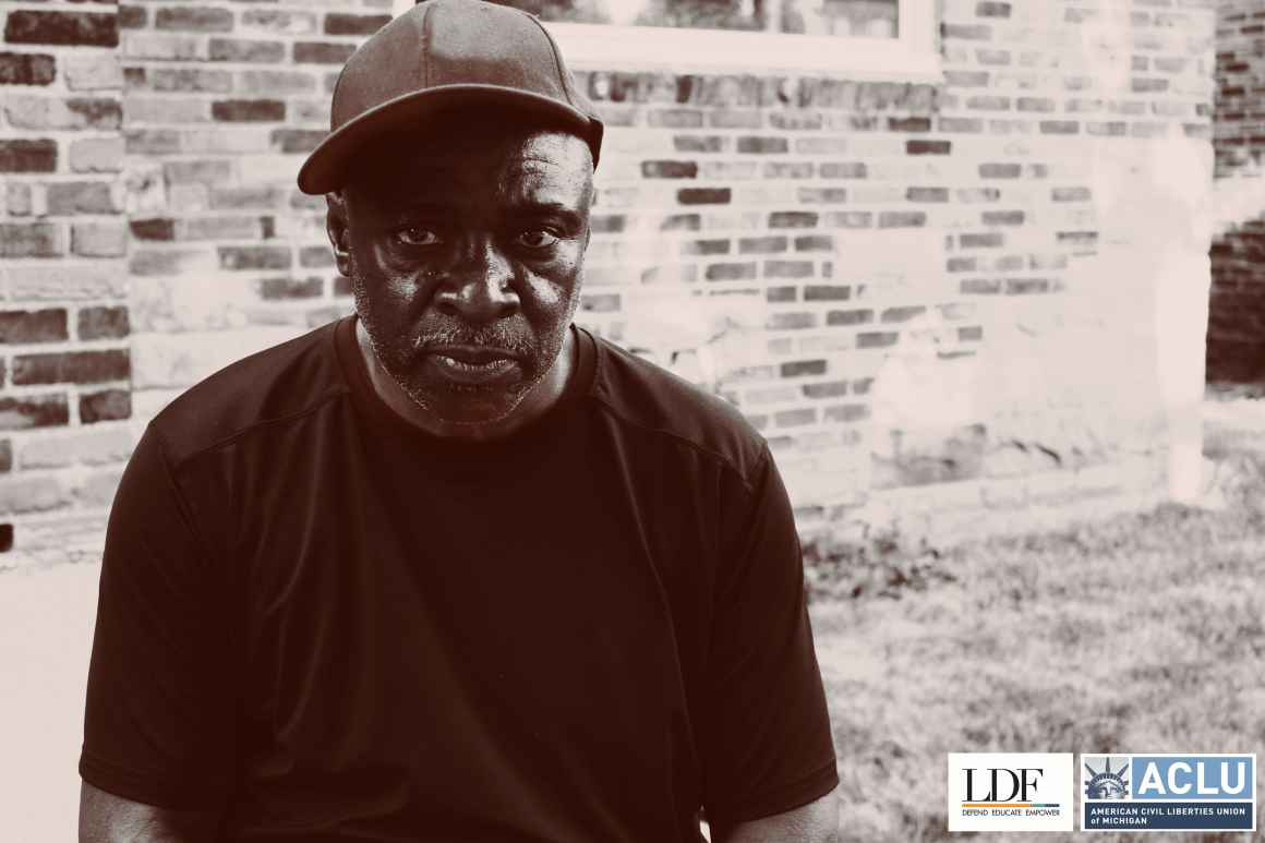 Walter Hicks sits in front of a brick wall, facing the camera. He has a serious expression and wears a baseball hat and black t-shirt.