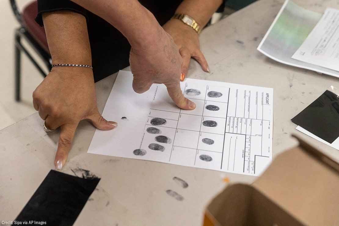 People inking their fingers for fingerprints on a paper.