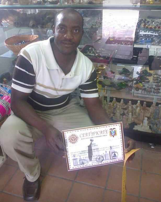 Ansly Damus kneels in a store holding a certificate