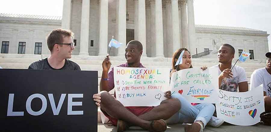 Five people sit on the ground in front of the Capitol holding LGBTQ protest signs and flags