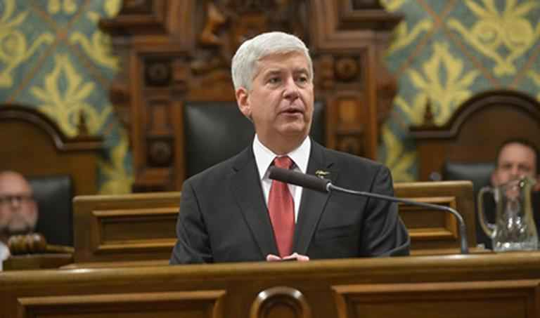 Governor Snyder sits behind a podium speaking into a microphone. He has close cropped grey hair and wears a suit with a red tie.