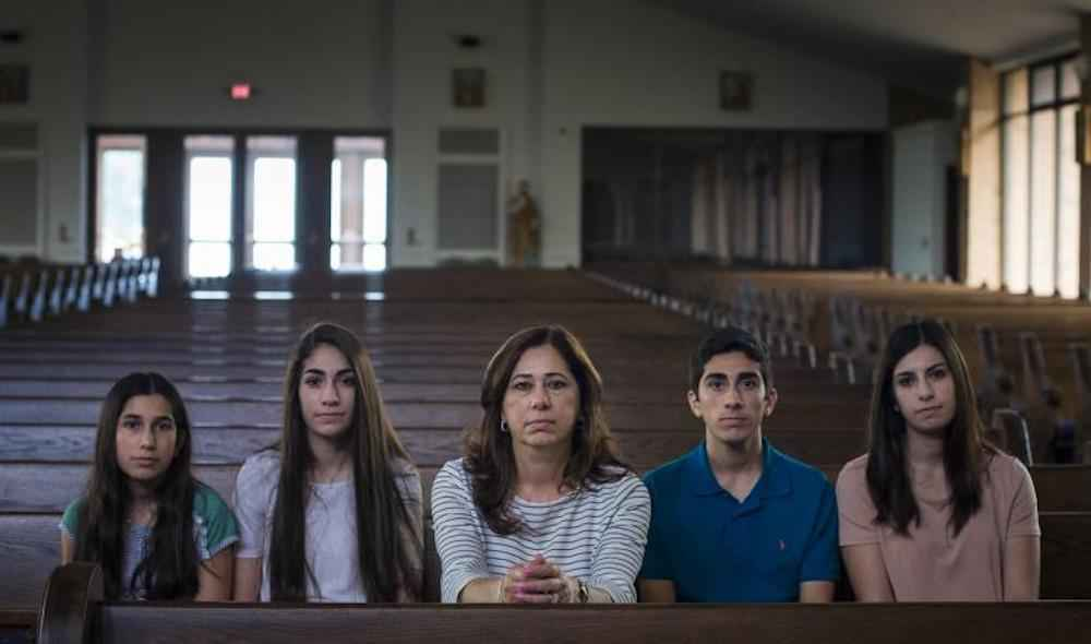 Portrait of the Hamama Family sitting in a pew in a church
