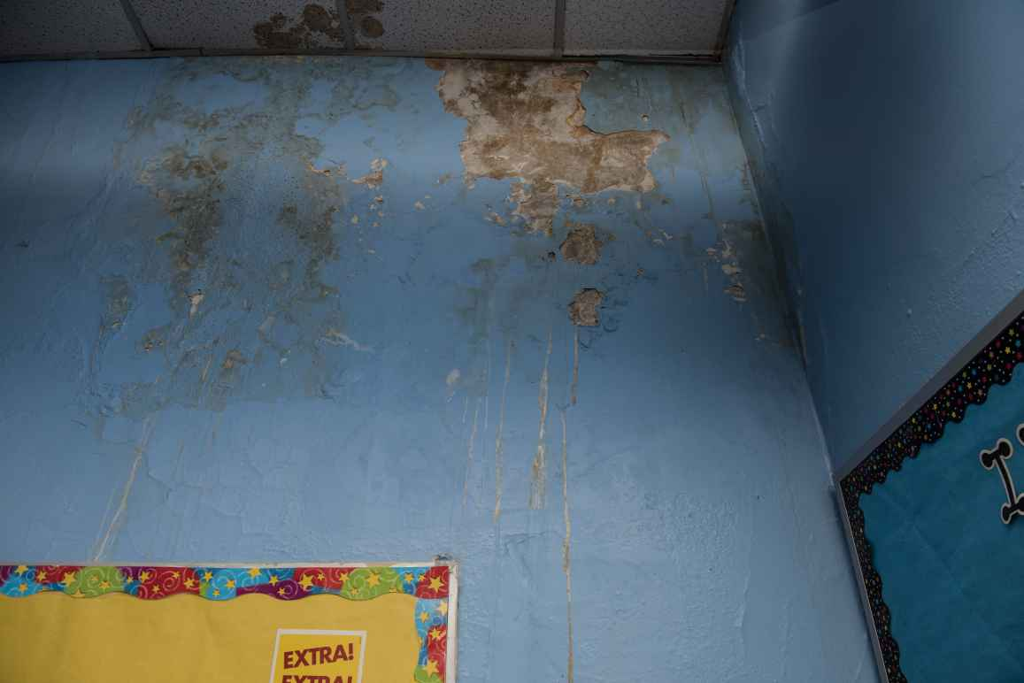 The corner of a blue wall and dropped ceiling with water damage. On the left is a bulletin board with yellow paper covering it and a starry border and on the right is a bulletin board with blue paper