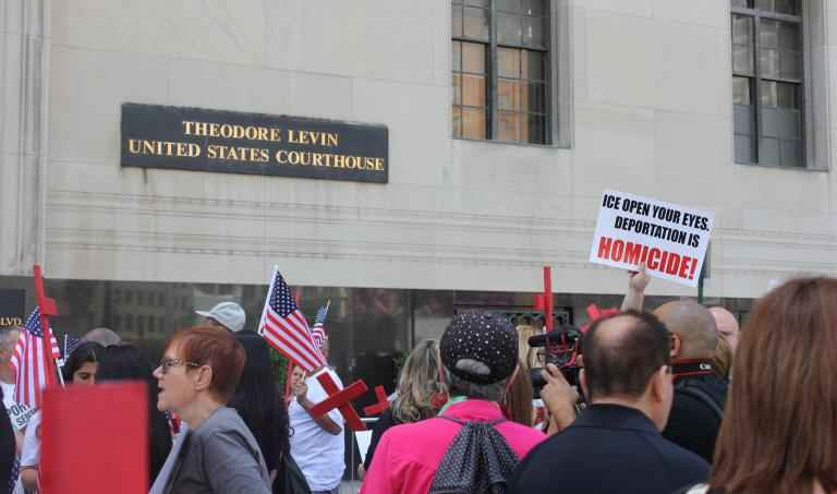 A crowd of protestors stand in front of the Theodore Levin US Courthouse holding anti-ICE protest signs and red crosses