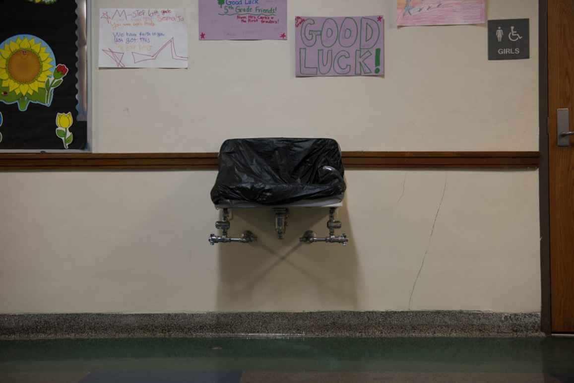 A drinking fountain covered with black plastic. Above it are hand-drawn posters wishing 5th graders good luck. On the left is a bulletin board with a black background and paper sunflower.