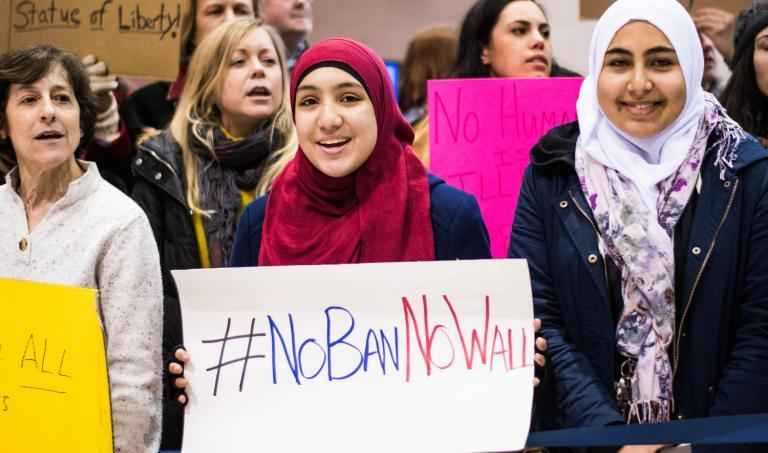 "woman wearing hijab holds sign that says ""No Ban, No Wall"""
