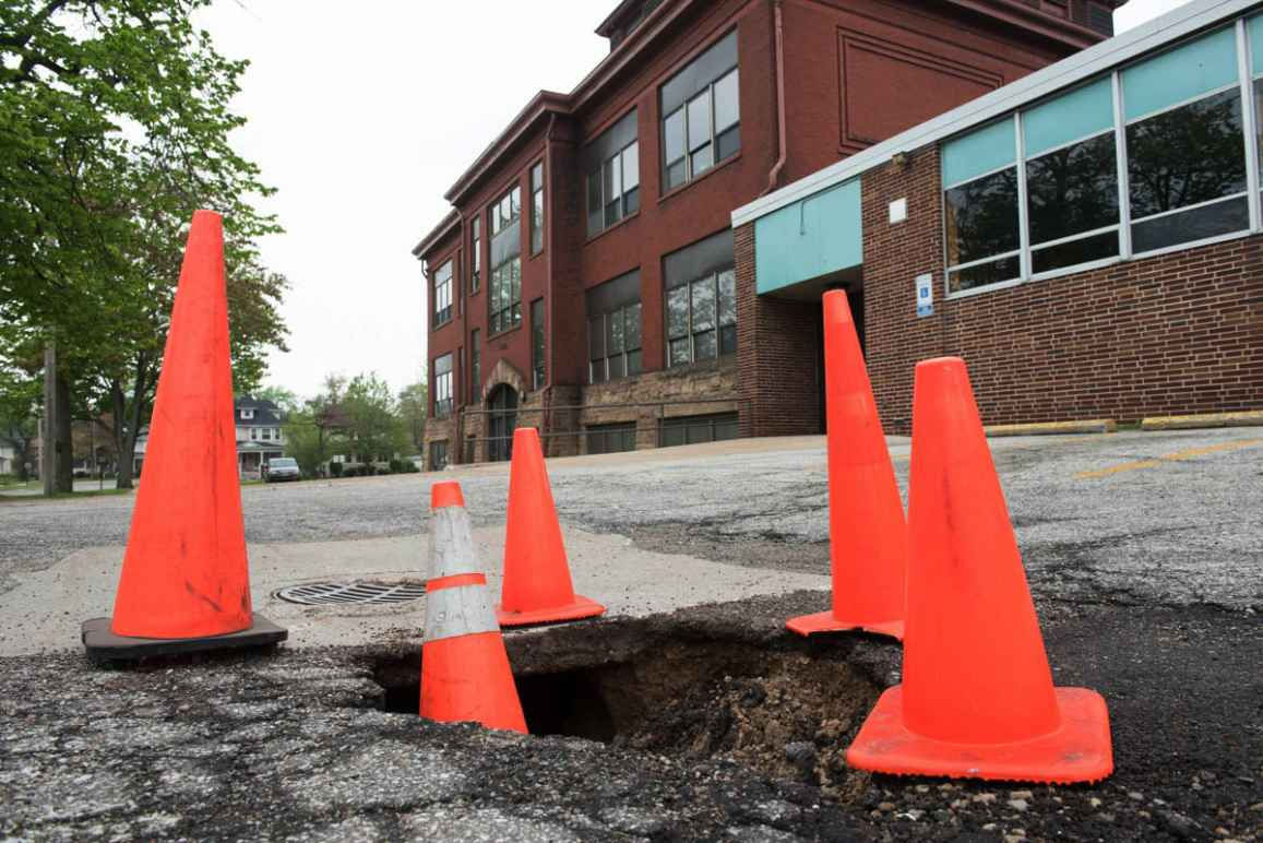 Orange traffic cones circle a hole in a road. In the background there is a red brick building on the right and a tall tree on the left