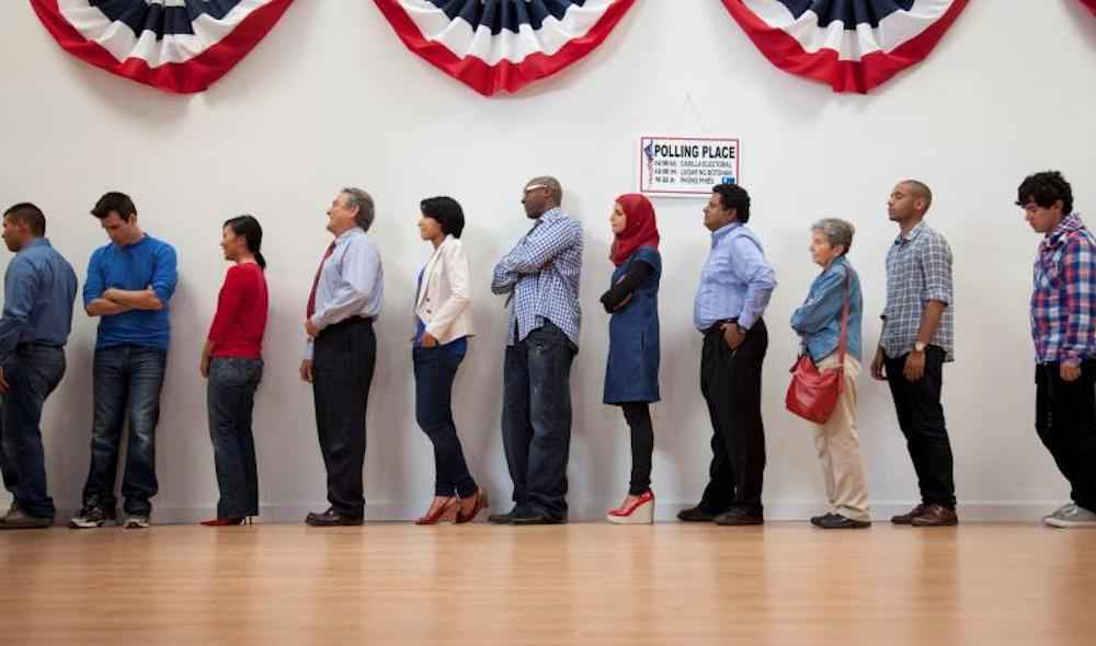 A line of people wait at their polling place beneath red, white and blue banners hanging on the wall