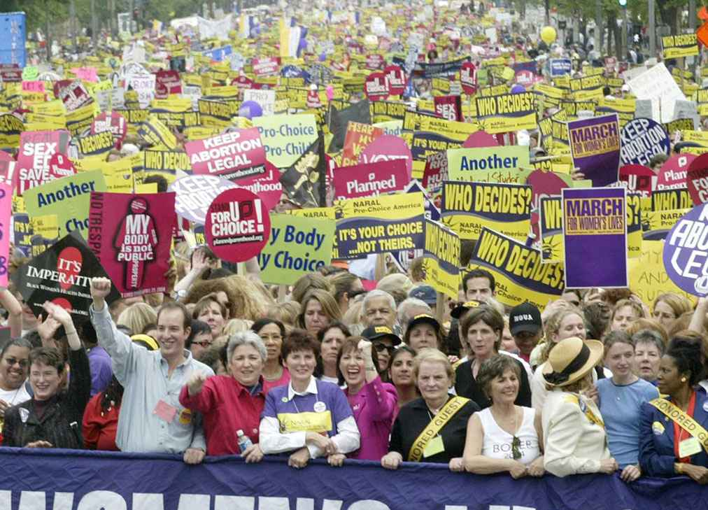 A group of people stand behind a barrier holding reproductive rights protest signs