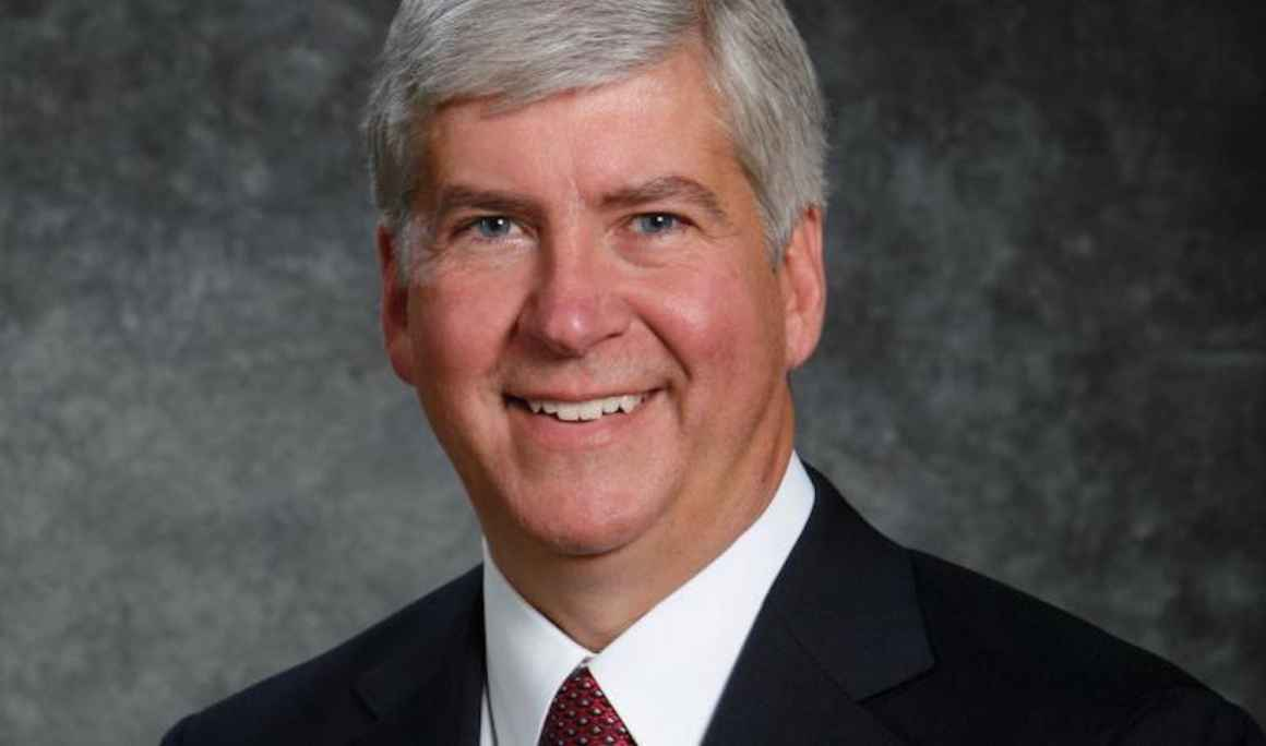A headshot of Governor Snyder. He has a big smile on his face, salt and pepper closely cropped hair and a suit with a red tie.