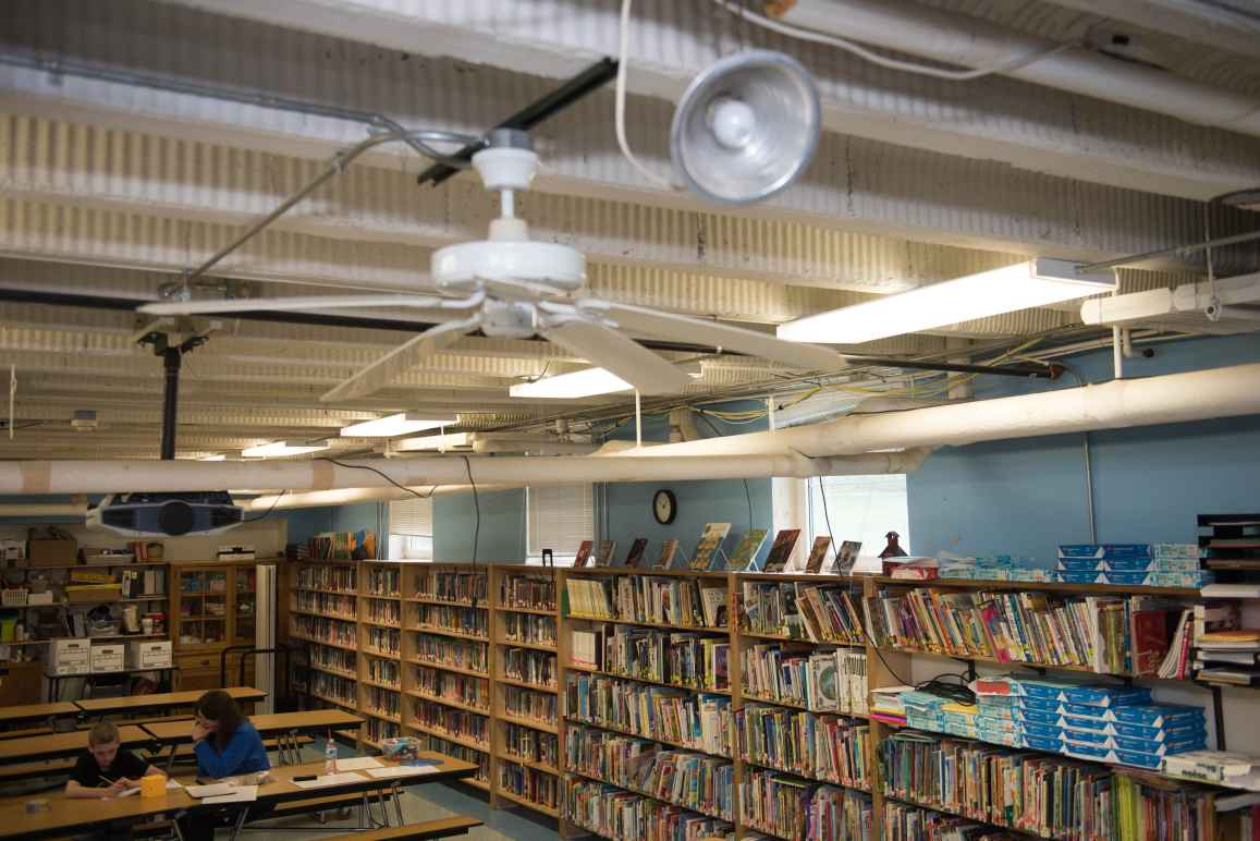 The Sodus library from above. A woman sits at a table on the left with a young boy. The shelves hold books, paper, and office equipment. The ceiling has a fan, clamp lamps, fluorescent lights and wiring.
